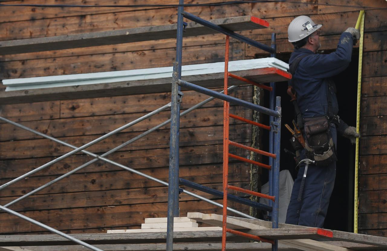 A construction worker takes measurements on a house in Lac-Megantic, November 21, 2013. The Canadian government allocated C$95 million ($90 million) on Thursday to help clean up contamination caused by the disastrous derailment in July of a train carrying crude oil through the small Quebec town of Lac-Megantic. REUTERS/Mathieu Belanger (CANADA - Tags: POLITICS BUSINESS CONSTRUCTION ENERGY TRANSPORT DISASTER)