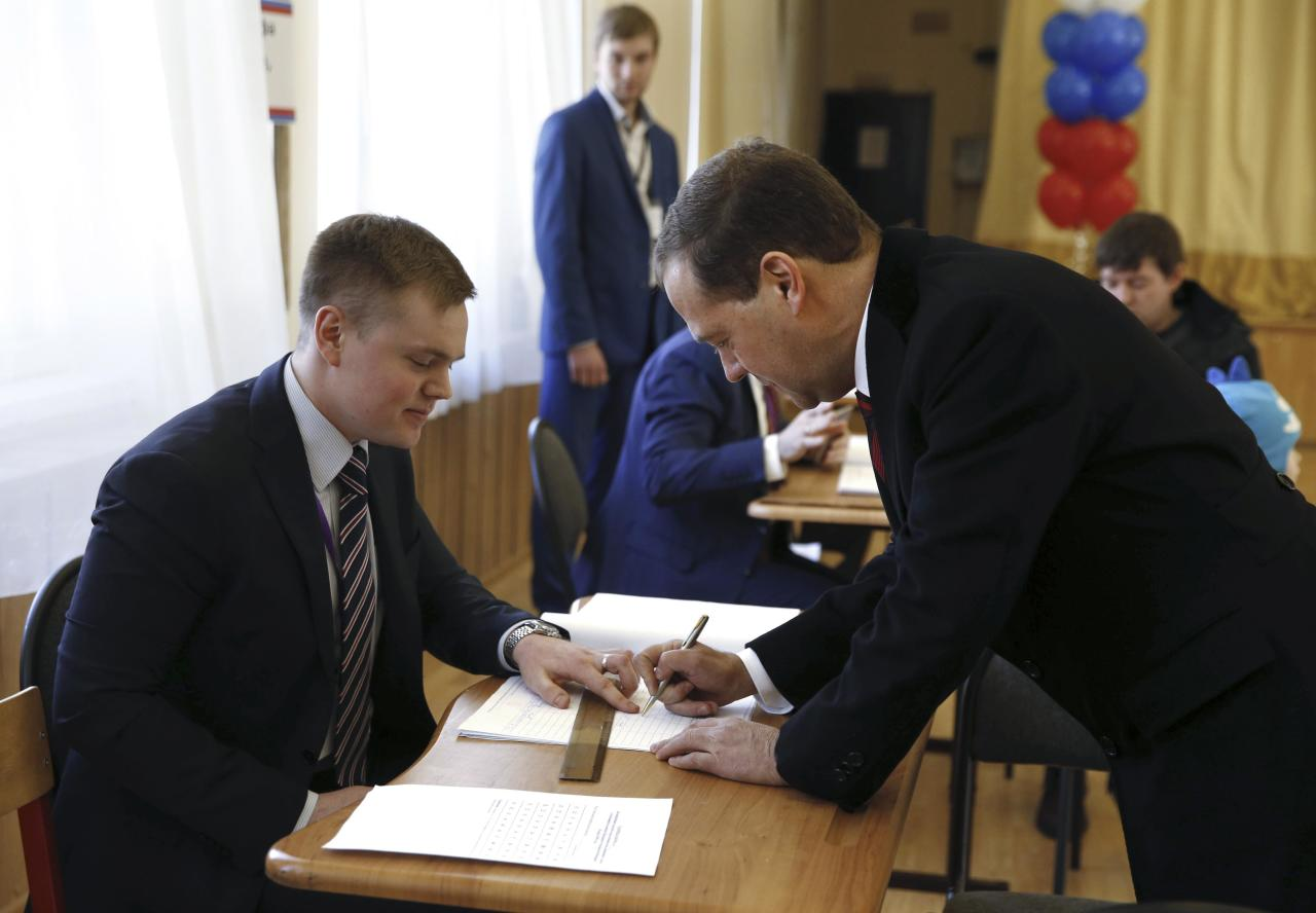 Russian Prime Minister Dmitry Medvedev (R) signs a document before receiving his ballot at a polling station during the presidential election in Moscow, Russia March 18, 2018. Sputnik/Dmitry Astakhov/Pool via REUTERS  ATTENTION EDITORS - THIS IMAGE WAS PROVIDED BY A THIRD PARTY.