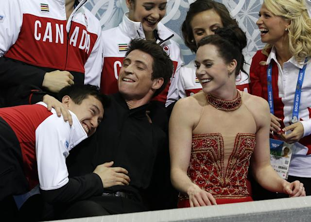 Scott Moir, centre, and Tessa Virtue second from right, both from Canada wait for their results with Patrick Chan, left, and the rest of the Canadian team after competing in the team free ice dance figure skating competition at the Iceberg Skating Palace during the 2014 Winter Olympics, Sunday, Feb. 9, 2014, in Sochi, Russia. (AP Photo/David J. Phillip )