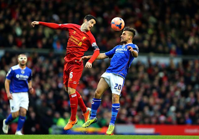 Liverpool's Luis Alberto, left, and Oldham's Mike Petrasso jump for the ball during their English FA Cup third round soccer match at Anfield, Liverpool, England, Sunday, Jan. 5, 2014. (AP Photo/Peter Byrne, PA Wire)