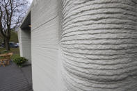 Exterior view showing the printer layers of the 3D-printed 94-square meters (1,011-square feet) two-bedroom bungalow resembling a boulder with windows in Eindhoven, Netherlands, Friday, April 30, 2021. The fluid, curving lines of its gray walls look natural. But they are actually at the cutting edge of housing construction in the Netherlands and around the world. They were 3D printed at a nearby factory. (AP Photo/Peter Dejong)