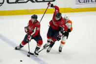 Washington Capitals defenseman Dmitry Orlov (9) gets tangled up between Washington Capitals left wing Daniel Carr (28) and Philadelphia Flyers right wing Nicolas Aube-Kubel (62) during the third period of an NHL hockey game, Friday, May 7, 2021, in Washington. The Flyers won 4-2. (AP Photo/Alex Brandon)