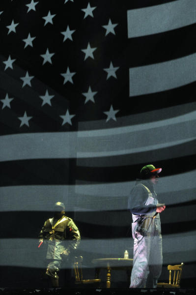 Big Boi, left, and Andre 3000 of hip hop group Outkast perform behind a screen depicting the American flag during their headlining set on the first day of the 2014 Coachella Music and Arts Festival on Friday, April 11, 2014, in Indio, Calif. (Photo by Chris Pizzello/Invision/AP)