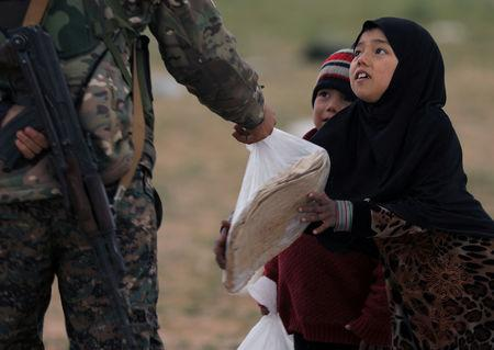 A girl takes a stack of bread from a fighter of Syrian Democratic Forces (SDF) near the village of Baghouz, Deir Al Zor province, Syria February 27, 2019. REUTERS/Rodi Said