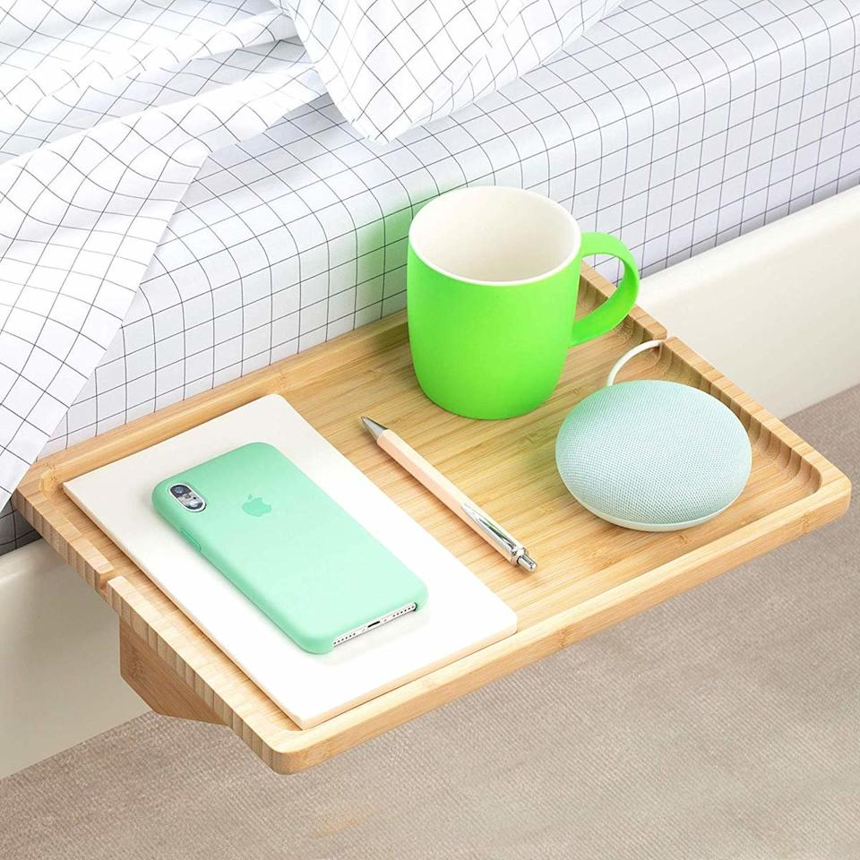 "<p>This minimalist bamboo shelf clamps directly onto the side of your bed frame, without taking up an inch of wall or floor space. Notches on the side of the shelf prevent charging cords from slipping onto the floor. </p> <p><strong>To buy: </strong>$25, <a href=""https://www.amazon.com/BedShelfie-Original-Bedside-Shelf-Business/dp/B07MPS3C8J?ie=UTF8&camp=1789&creative=9325&linkCode=as2&creativeASIN=B07MPS3C8J&tag=reasim03-20&ascsubtag=d41d8cd98f00b204e9800998ecf8427e"" target=""_blank"">amazon.com</a>. </p>"