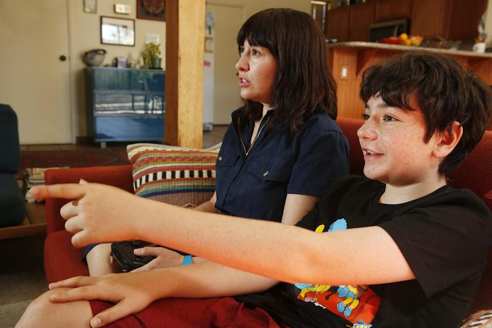 A woman and a boy play a video game sitting on a couch.