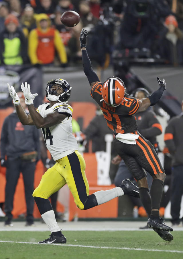 Cleveland Browns cornerback Denzel Ward (21) tips ball away from Pittsburgh Steelers wide receiver Tevin Jones (14) during the first half of an NFL football game Thursday, Nov. 14, 2019, in Cleveland. The ball was intercepted by Browns' Morgan Burnett. (AP Photo/Ron Schwane)
