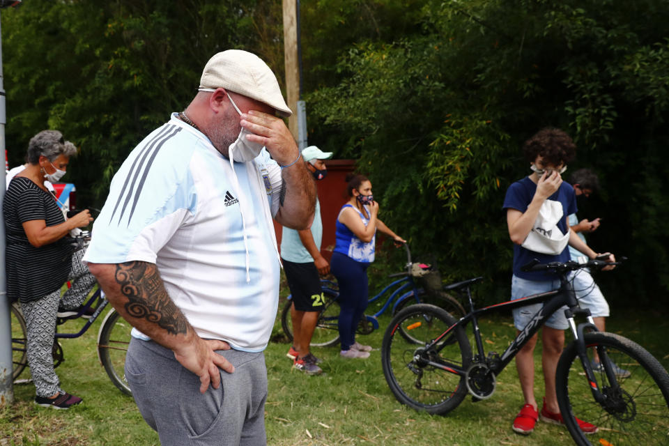 Mourners gather outside the home of Diego Maradona, in Buenos Aires, Argentina, Wednesday, Nov. 25, 2020. The Argentine soccer great who was among the best players ever and who led his country to the 1986 World Cup title before later struggling with cocaine use and obesity, died from a heart attack on Wednesday at his home in Buenos Aires. He was 60. (AP Photo/Marcos Brindicci)