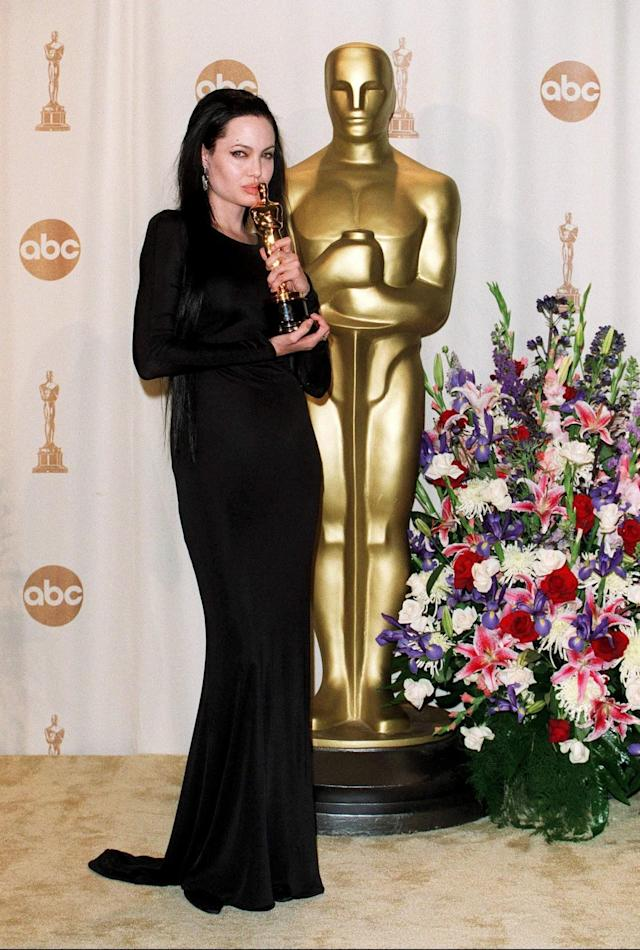 <p>Angelina Jolie made a serious goth statement in 2000, picking up her first Academy Award in a long-sleeved black Versace gown with long black hair extensions. (Photo: Rex) </p>