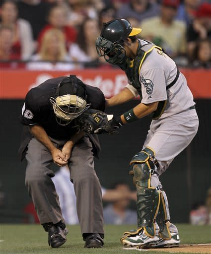 Home plate umpire Tom Hallion is comforted by Oakland Athletics catcher Kurt Suzuki after being hit by a foul tip during the first inning of a baseball game against the Los Angeles Angels in Anaheim, Calif., Monday, May 14, 2012. (AP Photo/Chris Carlson)
