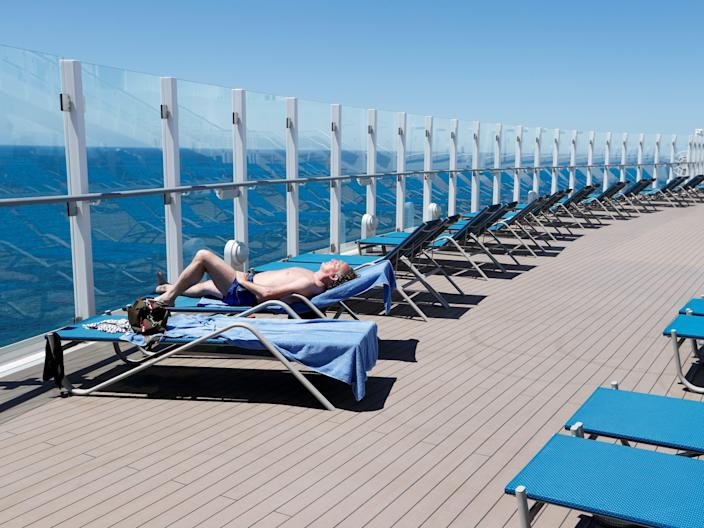 This image shows a line of blue beach chairs on the edge of a cruise ship with a man sunbathing on the left side. It shows the ocean on the far left side and blue skies across the top.