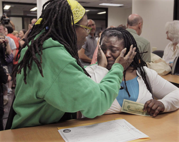 In this June 1, 2011 file photo, Janean Watkins, left, and Lakeesha Harris embrace after being the first in line to obtain a civil union license from the Cook County Office of Vital Records in Chicago. They are among more than two dozen same-sex couples filing lawsuits Wednesday, May 30, 2012, challenging the constitutionality of Illinois' marriage laws. Advocates for the American Civil Liberties Union of Illinois and Lambda Legal are each filing a lawsuit on behalf of the couples. Their goal is to make same-sex marriage legal. (AP Photo/M. Spencer Green, File)
