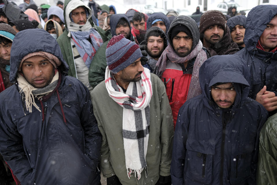 Migrants wait to be relocated during a snowfall at the Lipa camp northwestern Bosnia, near the border with Croatia, Saturday, Dec. 26, 2020. Hundreds of migrants are stranded in a burnt-out squalid camp in Bosnia as heavy snow fell in the country and temperatures dropped during a winter spell of bad weather after fire earlier this week destroyed much of the camp near the town of Bihac that already was harshly criticized by international officials and aid groups as inadequate for housing refugees and migrants.(AP Photo/Kemal Softic)