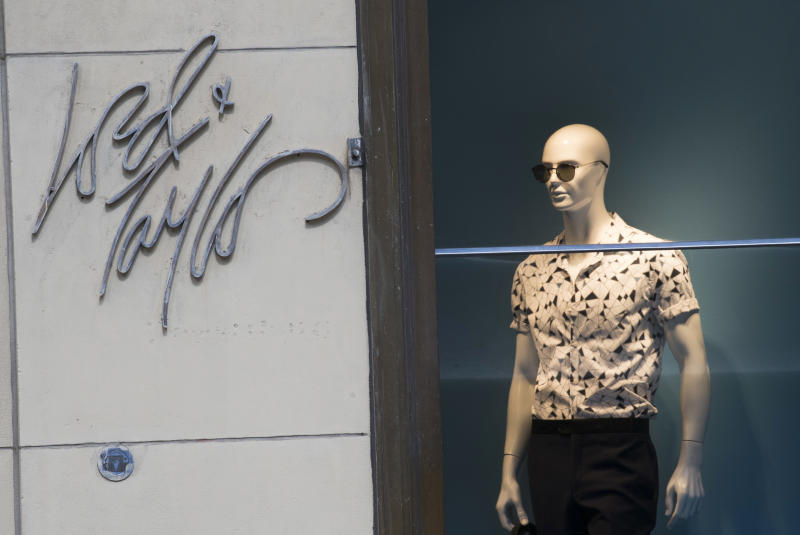 FILE - In this June 6, 2018, file photo the Lord & Taylor logo is seen next to a mannequin in a window display at their flagship store on Fifth Avenue in New York. Lord & Taylor, one of the nation's oldest department stores, is being sold for $100 million. The retailer's owner, Hudson's Bay Co., says it reached a deal with online rental clothing company Le Tote Inc. (AP Photo/Mary Altaffer, File)