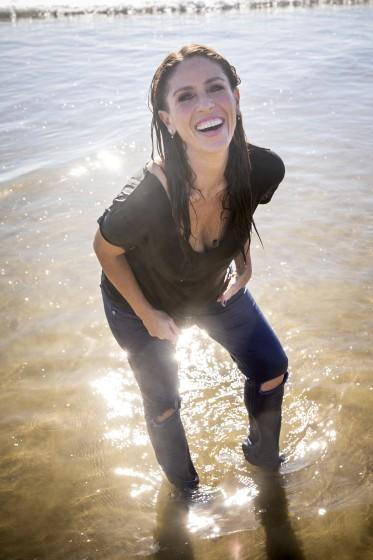 A smiling woman standing in the water in a brown t-shirt and blue jeans at the beach