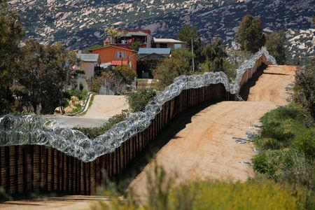 The border wall between the U.S. and Mexico is shown from the U.S. side near Tecate, California