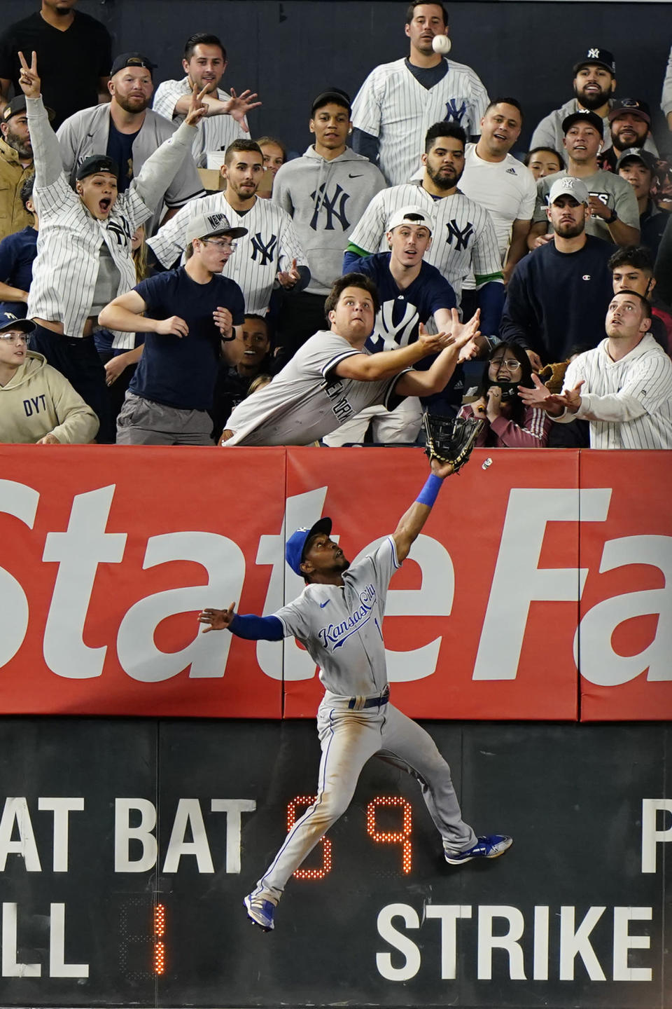 RETRANSMISSION TO CORRECT FROM DOUBLE TO TRIPLE - Kansas City Royals left fielder Jarrod Dyson (1) leaps for New York Yankees Luke Voit's seventh inning triple as fans reach for it in a baseball game Tuesday, June 22, 2021, at Yankee Stadium in New York. (AP Photo/Kathy Willens)