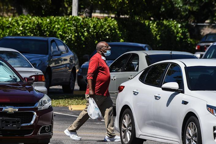 An elderly man picks up his lunch at John Knox Village, a retirement community in Pompano Beach about 40 miles north of Miami.