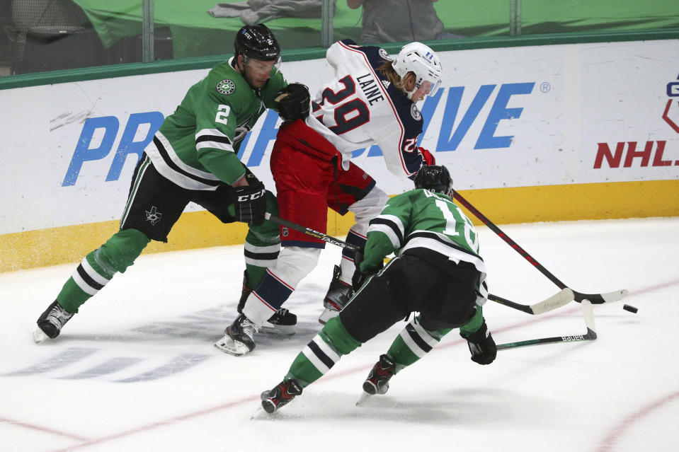 Dallas Stars defenseman Jamie Oleksiak (2) and center Jason Dickinson (18) try to get the puck away from Columbus Blue Jackets right wing Patrik Laine (29) during the first period of an NHL hockey game Thursday, April 15, 2021, in Dallas. (AP Photo/Richard W. Rodriguez)
