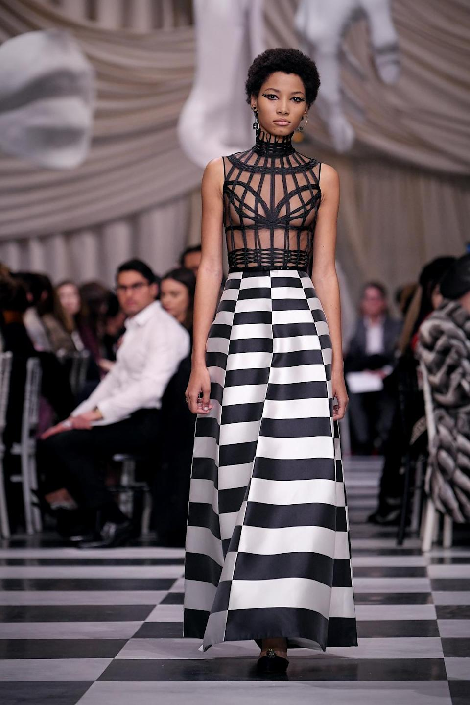 <p>Model wears a black caged bodice and black and white checkered skirt from the Dior Haute Couture SS18 collection. (Photo: Getty) </p>