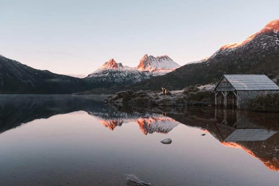 """<p>Frosted mountain peaks reflect on the waters of Cradle Mountain Lake in St. Clair National Park.</p><p><strong>Related: <a href=""""https://www.redbookmag.com/life/g32293087/australian-outback-photos/"""" rel=""""nofollow noopener"""" target=""""_blank"""" data-ylk=""""slk:These Photos of the Australian Outback Bring Social Distancing to a Whole Other Level"""" class=""""link rapid-noclick-resp"""">These Photos of the Australian Outback Bring Social Distancing to a Whole Other Level</a></strong></p>"""