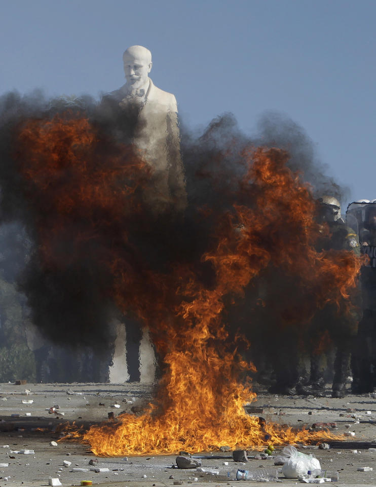 Fire and smoke from an exploded firebomb partially obscure the statue of Greek statesman Eleftherios Venizelos outside the Greek Parliament during clashes in Athens, Wednesday, Oct. 19, 2011. Greek anger over new austerity measures and layoffs erupted into violence on Wednesday, as demonstrators hurled chunks of marble and gasoline bombs and riot police responded with tear gas and stun grenades that echoed across Athens' main square. Wednesday was the first day of a two-day general strike that unions described as the largest protests in years, with at least 100,000 people marching through central Athens. (AP Photo/Thanassis Stavrakis)