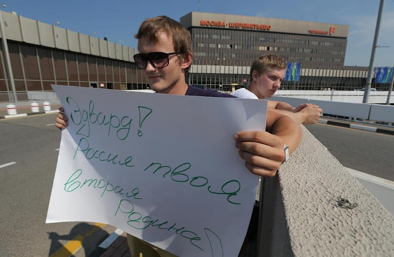 A supporter of National Security Agency leaker Edward Snowden holds a poster outside Sheremetyevo airport in Moscow Friday, June 28, 2013. Russian and foreign journalists continued to monitor the Sheremetyevo international airport, where Snowden is believed to remain at the transit zone. The poster reads : Edward! Russia is your second Motherland! (AP Photo/Sergei Grits)