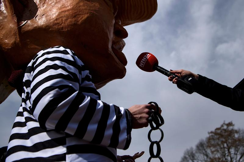 An activist dressed as an of effigy of US President Donald Trump is interviewed while protesting during Presidents' Day in Lafayette Square near the White House on Feb. 18, 2019 in Washington, D.C. (Photo: Brendan Smialowski/AFP/Getty Images)