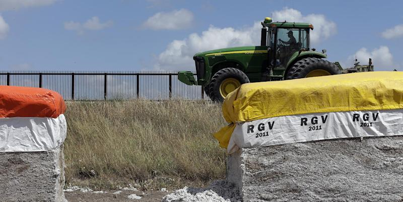 In this Sept. 6, 2012, photo, a tractor is used to farm in cotton field along a U.S.-Mexico border fence that passes through the property in Brownsville, Texas. Since 2008, hundreds of landowners on the border have sought fair prices for property that was condemned to make way for the fence, but many of them received initial offers that were far below market value. (AP Photo/Eric Gay)