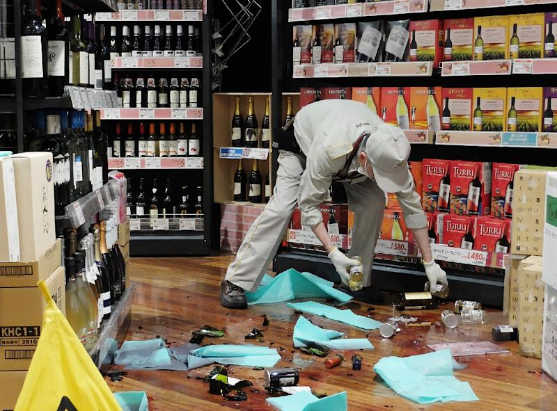 A shop employee clears broken bottles following an earthquake near Osaka western Japan