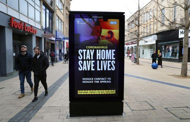 People walk past a 'Stay Home Save Lives' sign on Broadmead in Bristol during England's third national lockdown to curb the spread of coronavirus