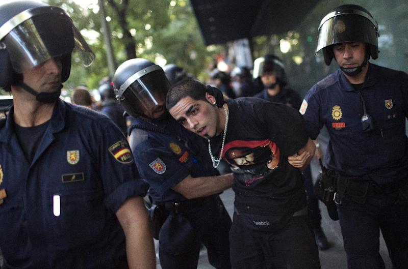 A demonstrator is arrested by police officers during a protest against the recent austerity measures announced by the Spanish government, in front of the Popular Party in Madrid, Spain, on Friday July 13, 2012.  Thousands of demonstrators took to the streets Friday to protest their second wave of wage cuts in as many years as the government prepared to approve austerity measures that include those reductions as part of a deficit-cutting plan to save euro 65 billion through 2015. (AP Photo/Emilio Morenatti)