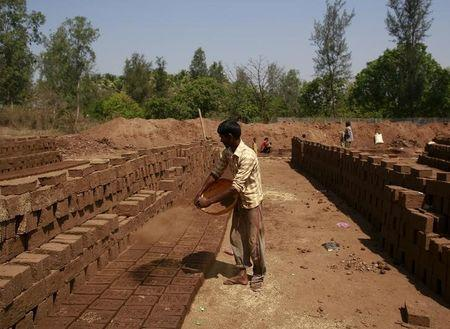 A labourer throws mud on bricks kept for drying at a kiln in Karjat, India, March 10, 2016. REUTERS/Danish Siddiqui