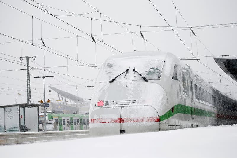 An ICE high-speed train is seen covered in snow at a train station in Dortmund