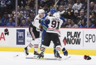 Vancouver Canucks' Tanner Pearson (70) and Chicago Blackhawks' Drake Caggiula (91) drop their gloves as they fight during the second period of an NHL hockey game Wednesday, Feb. 12, 2020, in Vancouver, British Columbia. (Darryl Dyck/The Canadian Press via AP)