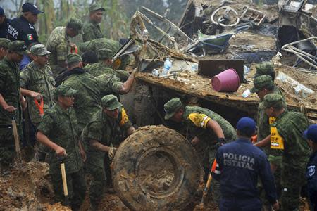 Soldiers and police work around the wreckage of a bus after it was buried by a mountain landslide at Altotonga in Veracruz state