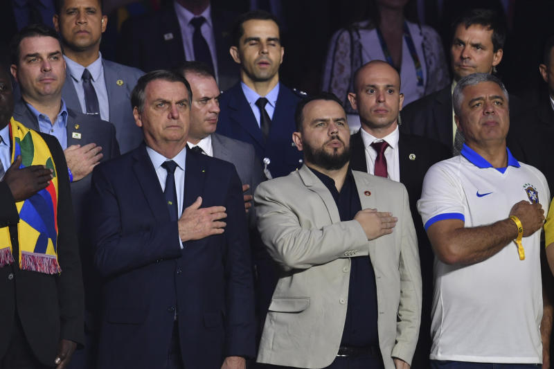 (L-R) Brazilian President Jair Bolsonaro, Sao Paulo's state deputy Gil Diniz and Sao Paulo's senator Major Olimpio listen to the national anthem before the start of the Copa America football tournament group match between Brazil and Boliva at the Cicero Pompeu de Toledo Stadium, also known as Morumbi, in Sao Paulo, Brazil, on June 14, 2019. (Photo by Pedro UGARTE / AFP) (Photo credit should read PEDRO UGARTE/AFP via Getty Images)