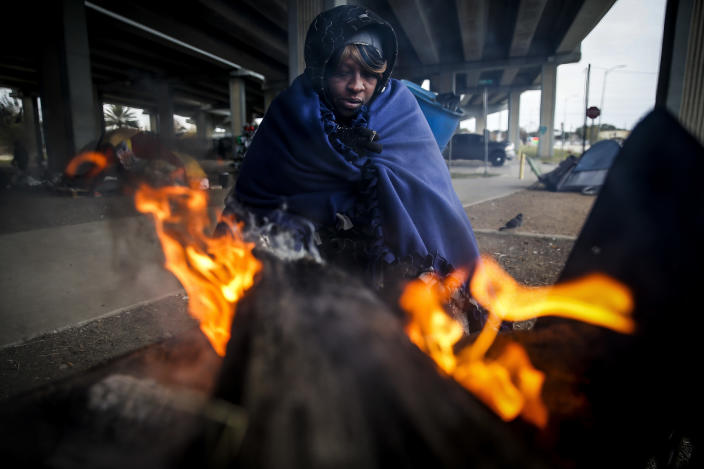 <p>Tony Sampson, who received a blanket from Star of Hope's Love in Action van, tries to warm up by a fire under the Eastex Freeway as temperatures hover in the 30s Tuesday, Jan. 2, 2018, in Houston. (Photo: Michael Ciaglo/Houston Chronicle via AP) </p>