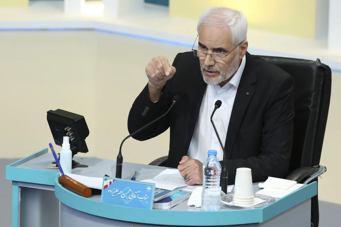 In this photo made available by the government-affiliated Young Journalists Club, presidential candidate Mohsen Mehralizadeh speaks in a televised debate in a state-run television studio, in Tehran, Iran, on Saturday, June 5, 2021. Elections are scheduled for June 18. (Morteza Fakhri Nezhad/YJC via AP)