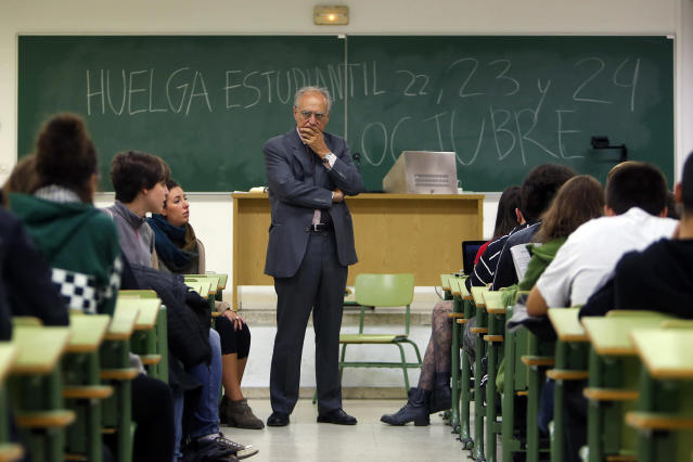 "<p>A professor stands in front of a blackboard where protesting students have written, ""Student Strike, 22, 23 and 24 of October,"" as students ask him to join the protest against increases in university tuition and budget cuts to education at Complutense University in Madrid, Oct. 22, 2013. (AP Photo/Andres Kudacki) </p>"