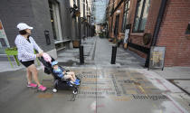 """A woman pushes a stroller with a child past the entrance to the alleyway to the Dairy Block that leads to the Maven Hotel Sunday, July 11, 2021, in lower downtown Denver. Authorities said four people have been arrested on drug and weapons charges after a """"report of a suspicious occurrence"""" at the downtown Denver hotel, which is located near Coors Field, the site of Major League Baseball's 2021 All-Star Game. Denver police said officers responding to a tip searched two rooms at the hotel on Friday night. (AP Photo/David Zalubowski)"""