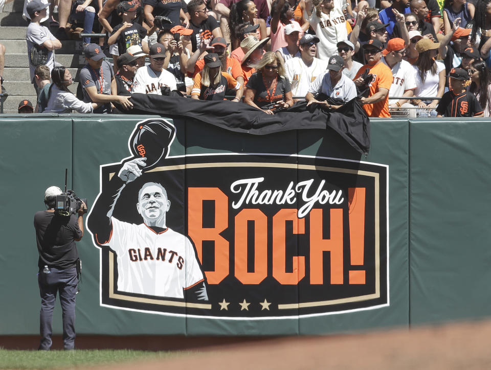 Fans unveil artwork on the left field wall dedicated to manager Bruce Bochy during the baseball game against the San Diego Padres Sunday, Sept. 1, 2019, in San Francisco. Bochy will retire from Major League baseball at the end of the 2019 season. (AP Photo/Ben Margot)