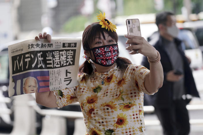 """A passer-by takes a selfie with an extra newspaper reporting on President-elect Joe Biden's win in the U.S. presidential election, in Tokyo Sunday, Nov. 8, 2020. The headline reads: """"Mr. Biden Assured to win.""""(AP Photo/Eugene Hoshiko)"""
