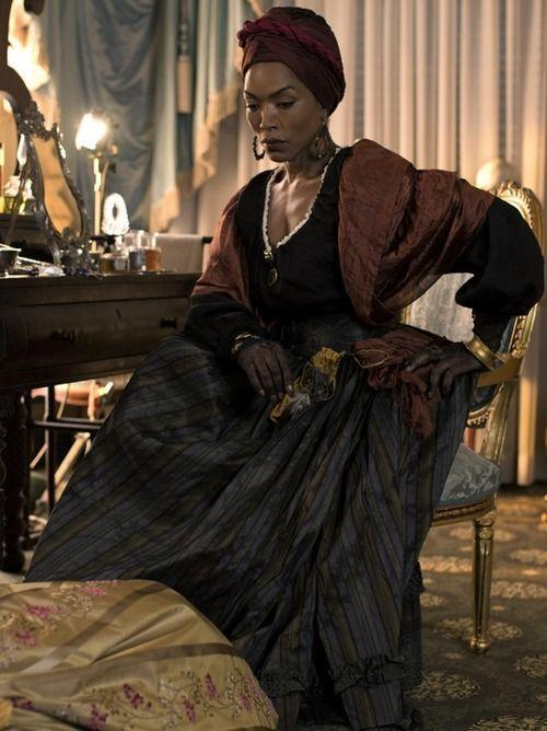 """<p>In <em>American Horror Story: Coven,</em> Angela Bassett plays Marie Laveau, who is actually based on a real-life person. Although not really a witch, she was a renowned Louisiana Creole practitioner of Voodoo as well as an herbalist and midwife.</p><p><a class=""""link rapid-noclick-resp"""" href=""""https://www.amazon.com/Womens-Stretch-Headband-Scarf-Turban/dp/B07XX16SG4/?tag=syn-yahoo-20&ascsubtag=%5Bartid%7C2164.g.37050429%5Bsrc%7Cyahoo-us"""" rel=""""nofollow noopener"""" target=""""_blank"""" data-ylk=""""slk:SHOP HEAD SCARVES"""">SHOP HEAD SCARVES</a></p><p><a class=""""link rapid-noclick-resp"""" href=""""https://www.amazon.com/Amazon-Essentials-Stainless-Flattened-Earrings/dp/B00E1GY6X6/?tag=syn-yahoo-20&ascsubtag=%5Bartid%7C2164.g.37050429%5Bsrc%7Cyahoo-us"""" rel=""""nofollow noopener"""" target=""""_blank"""" data-ylk=""""slk:SHOP HOOP EARRINGS"""">SHOP HOOP EARRINGS</a></p><p><a class=""""link rapid-noclick-resp"""" href=""""https://www.amazon.com/Eliza-Womens-Velvet-Jacquard-Ballgown/dp/B08HQFPKM4/?tag=syn-yahoo-20&ascsubtag=%5Bartid%7C2164.g.37050429%5Bsrc%7Cyahoo-us"""" rel=""""nofollow noopener"""" target=""""_blank"""" data-ylk=""""slk:SHOP ELEGANT DRESSES"""">SHOP ELEGANT DRESSES</a></p>"""
