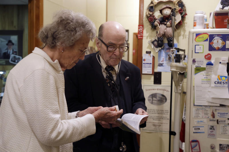 In this Tuesday, Oct. 30, 2012 photo, Dr. Russell Dohner, right, talks with nurse Rose Busby about a patient's prescription in Rushville, Ill. In an era of rising healthcare costs, the 87-year-old doctor only charges patients $5 per office visit and doesn't take insurance saying it isn't worth the bother. (AP Photo/Jeff Roberson)