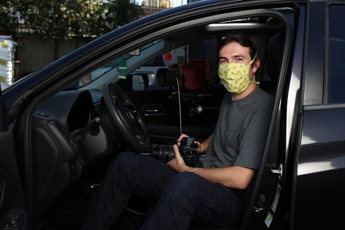 "Photographer Ian Byers-Gamber in his Honda, the vehicle that frames portraits he's shot during the pandemic. <span class=""copyright"">(Dania Maxwell / Los Angeles Times)</span>"