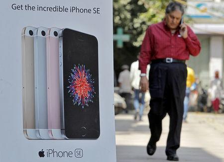 FILE PHOTO: A man speaks on his mobile phone as he walks past an Apple iPhone advertisement billboard on a street in New Delhi