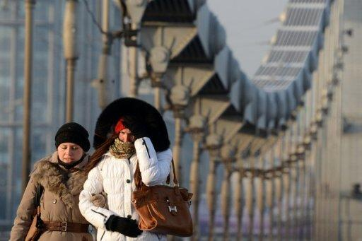 Young women brave the freezing outdoors as they walk near Krymsky Bridge in Moscow, on December 24, 2012