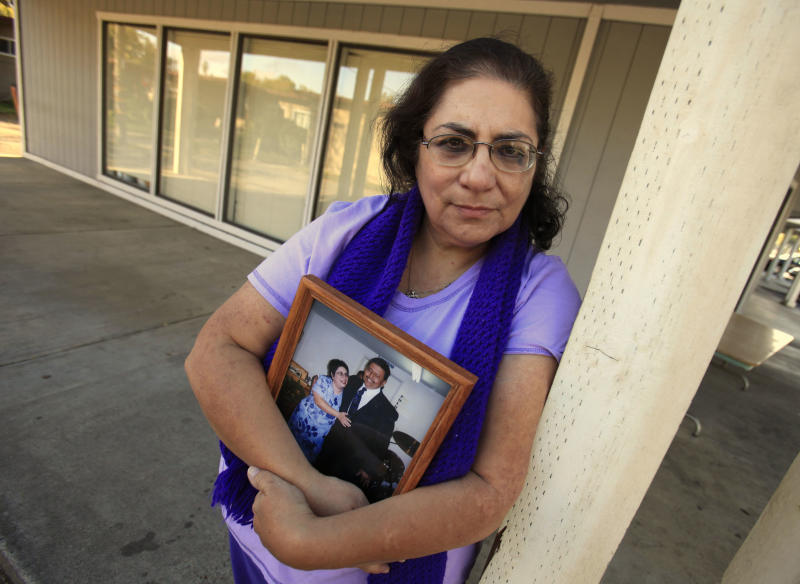 In this photo taken Nov. 4, 2011, Karen Carrisosa is seen with a photo of her and her husband Larry, at the site where he was killed in Sacramento, Calif.  Carrisosa  became concerned  when officials found a  Facebook posting from Corcoran State Prison inmate Fredrick Garner who is serving a 22-year, involuntary manslaughter sentence for killing Larry 11 years ago.   Carrisosa is a victim of a disturbing trend: Inmates who use smuggled mobile devices or work through third parties to access social networking sites giving them the ability to harass their victims and victim's families. (AP Photo/Rich Pedroncelli)