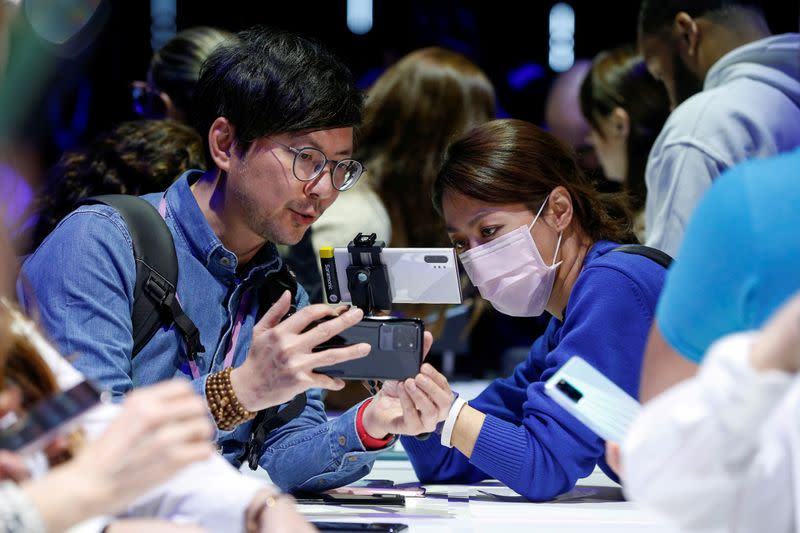 FILE PHOTO: Attendees look at a Samsung Galaxy S20 Ultra 5G smartphone during Samsung Galaxy Unpacked 2020 in San Francisco